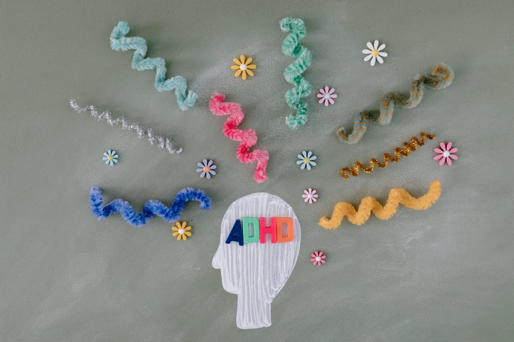 Zeichnung eines menschlichen Kopfes mit ADHS geschrieben und bunten Spiralen herum.