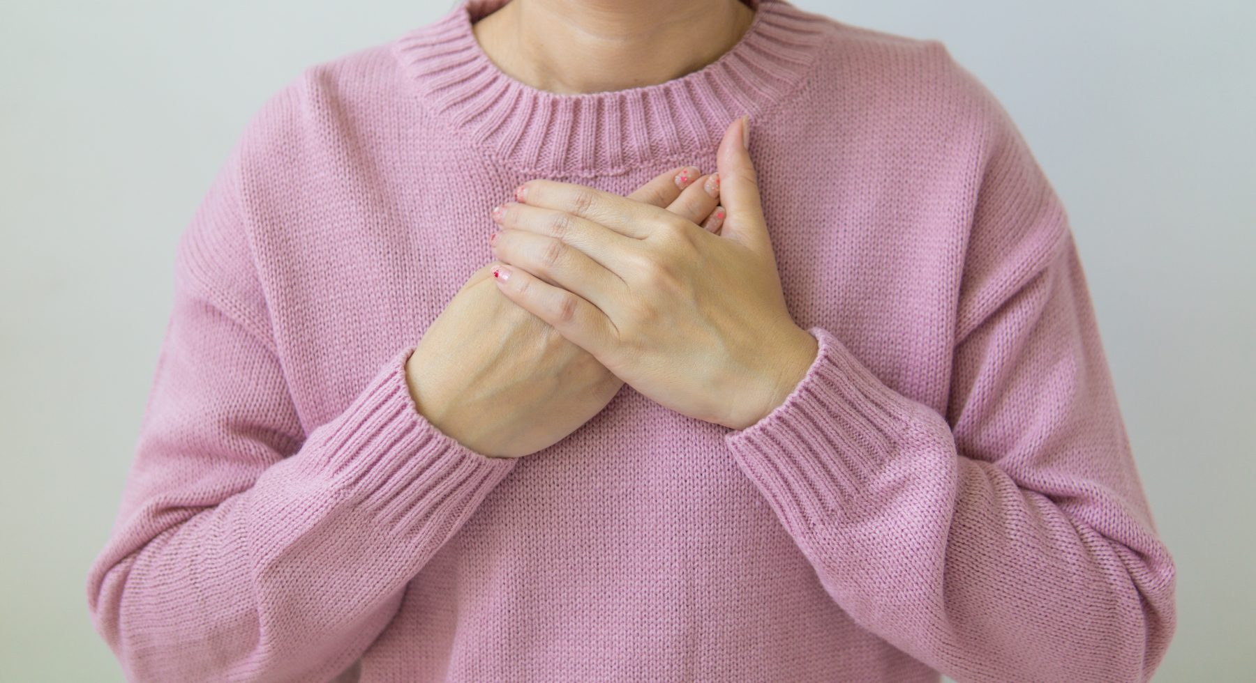 Eine Person mit den Händen auf der Brust.