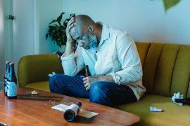 Mann sitzt auf seiner Couch mit einer Hand auf dem Kopf und einer Flasche in der anderen Hand.