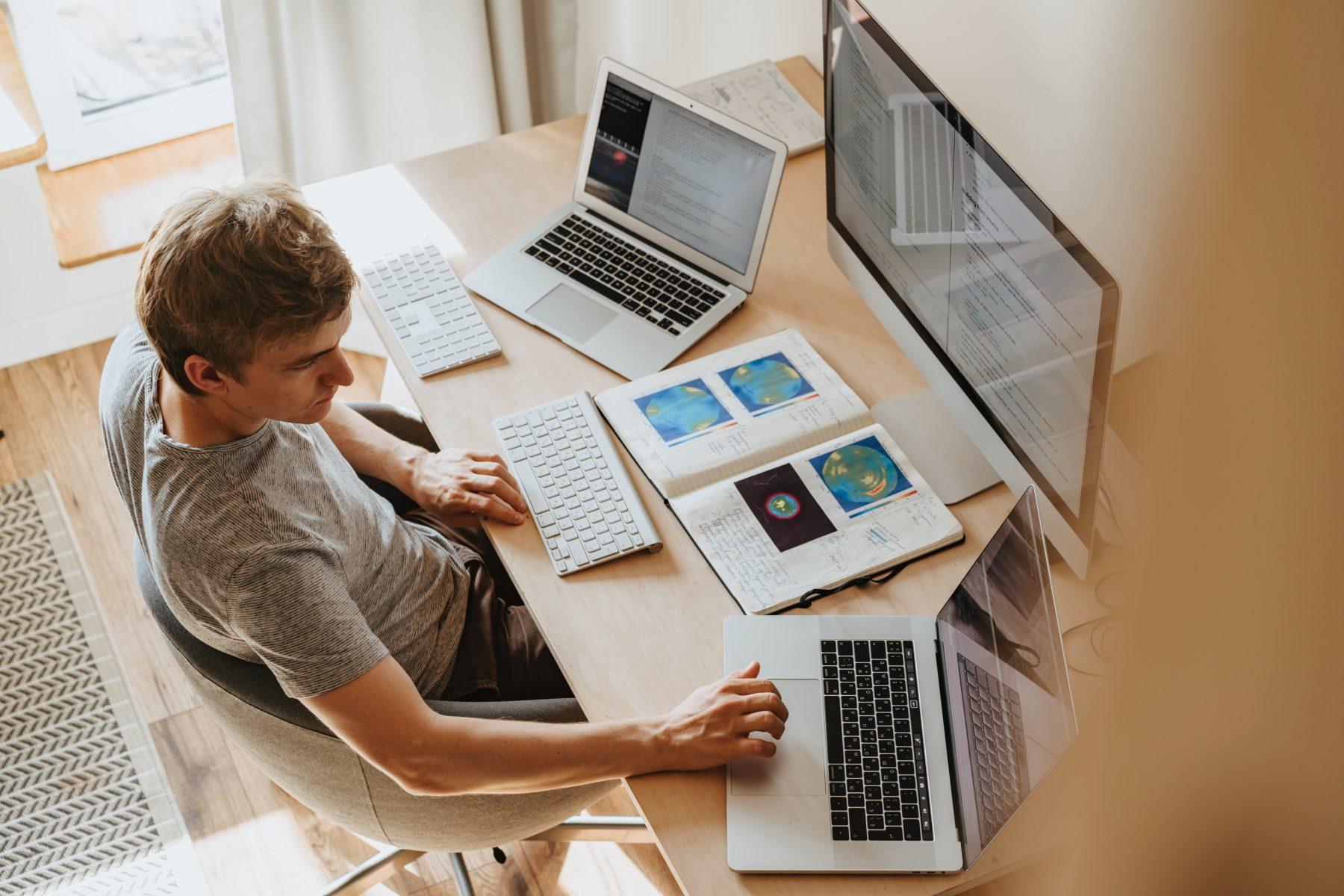 Person mit mehreren Laptops und einem Monitor vor sich.