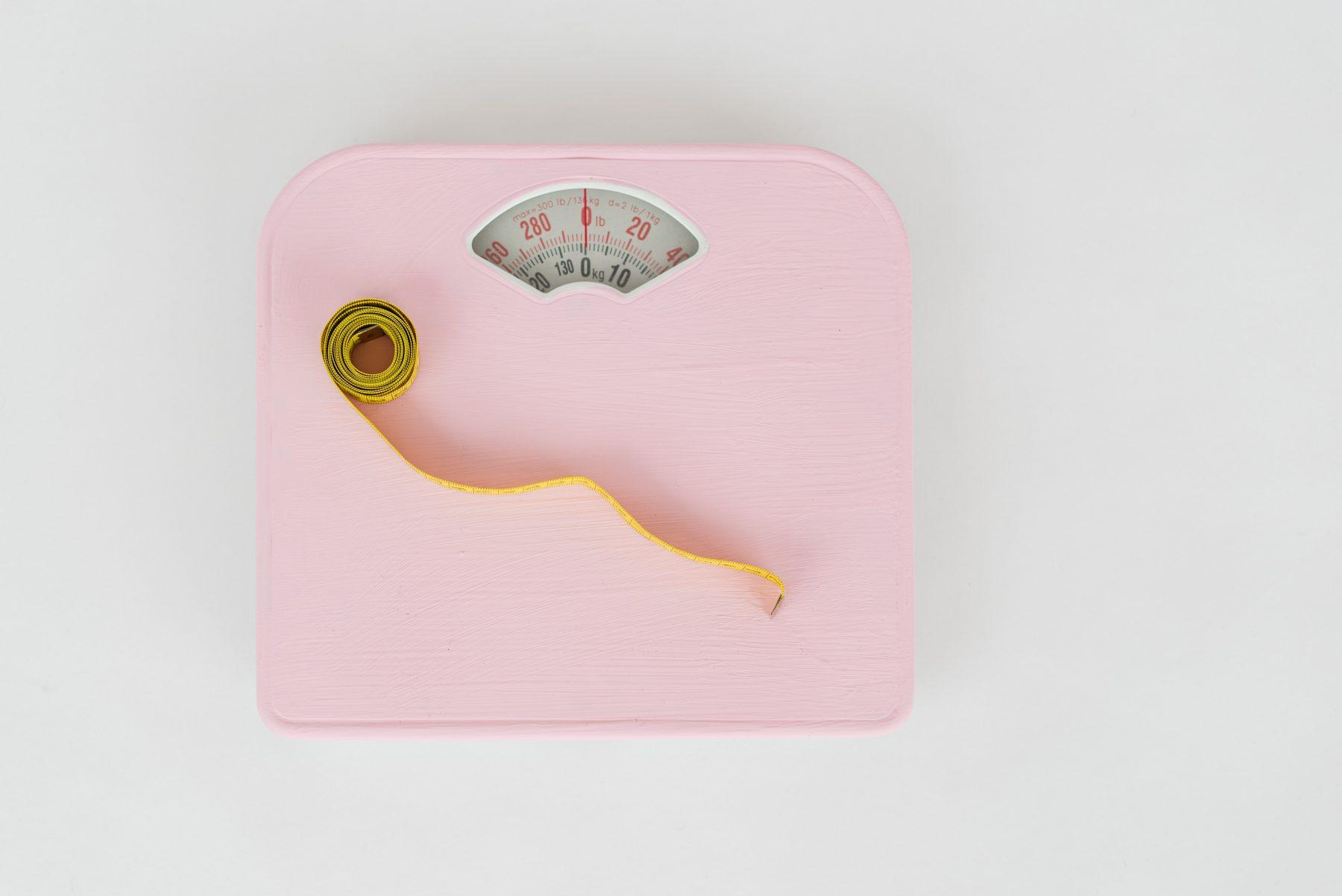 Maßband auf einer rosa Skala.