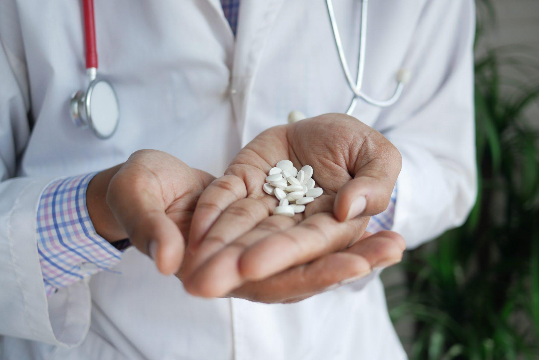 Ein Arzt, der weiße Pillen hält.