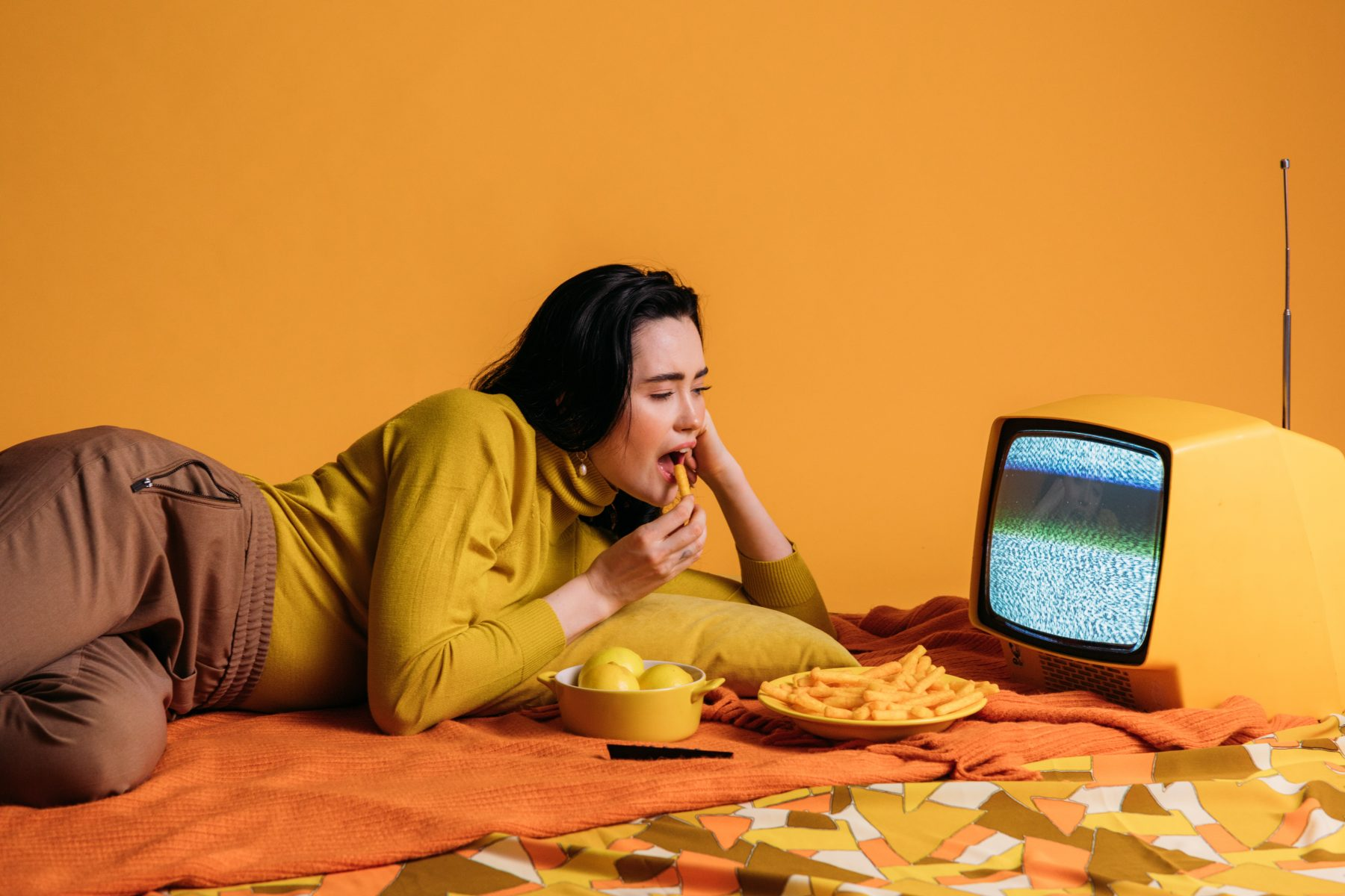 Frau isst, während sie auf einen Fernseher starrt.