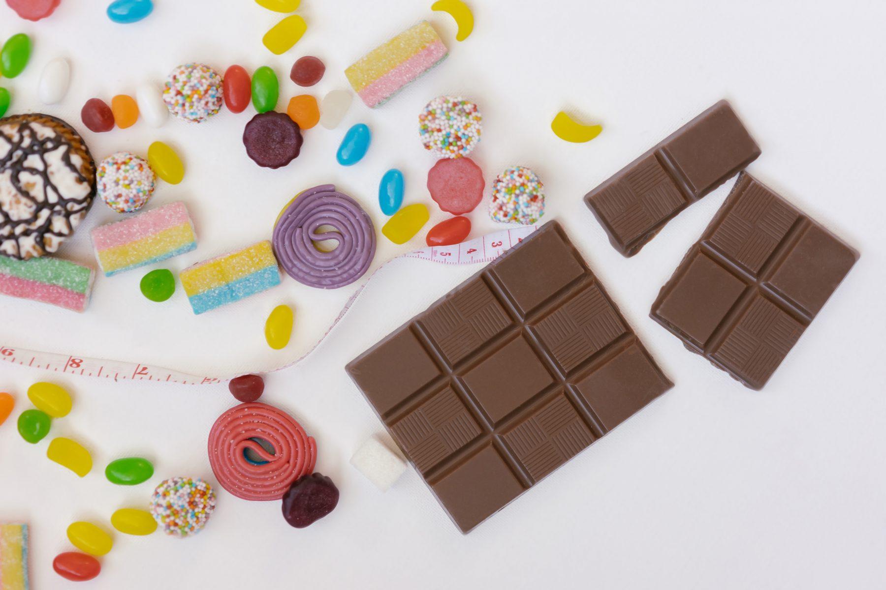 Bunte Süßigkeiten, Maßband und Schokoriegel mit weißem Hintergrund.