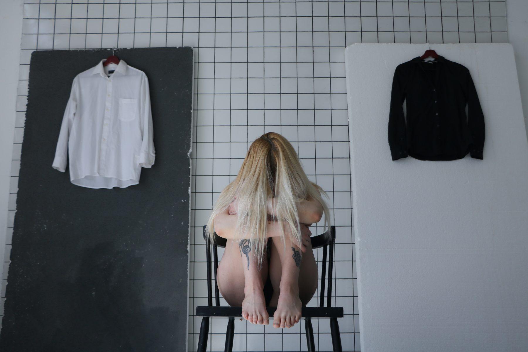 Frau sitzt auf einem Stuhl mit dem Kopf auf den Beinen.