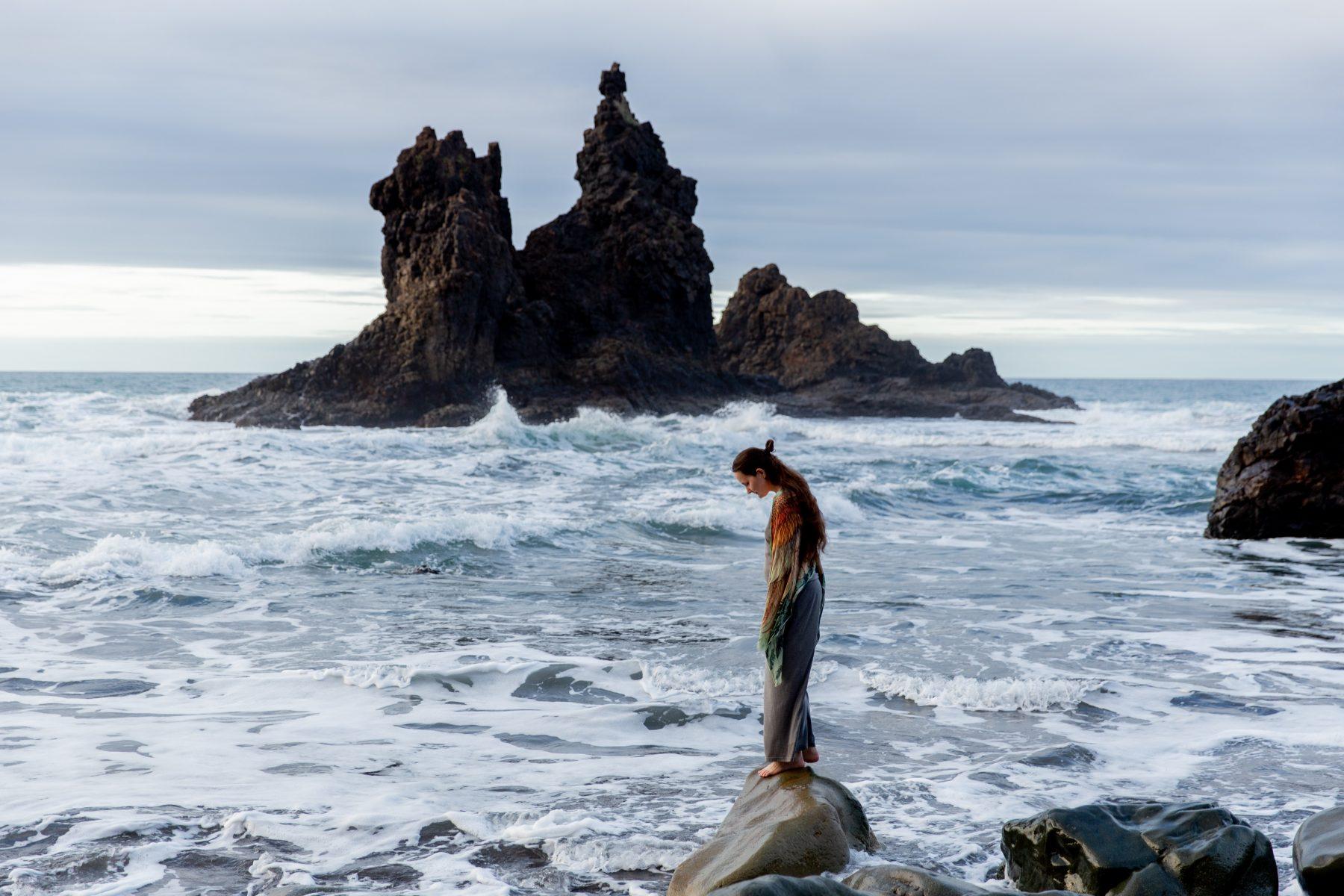 Person, die allein auf den Felsen vor dem Meer steht.