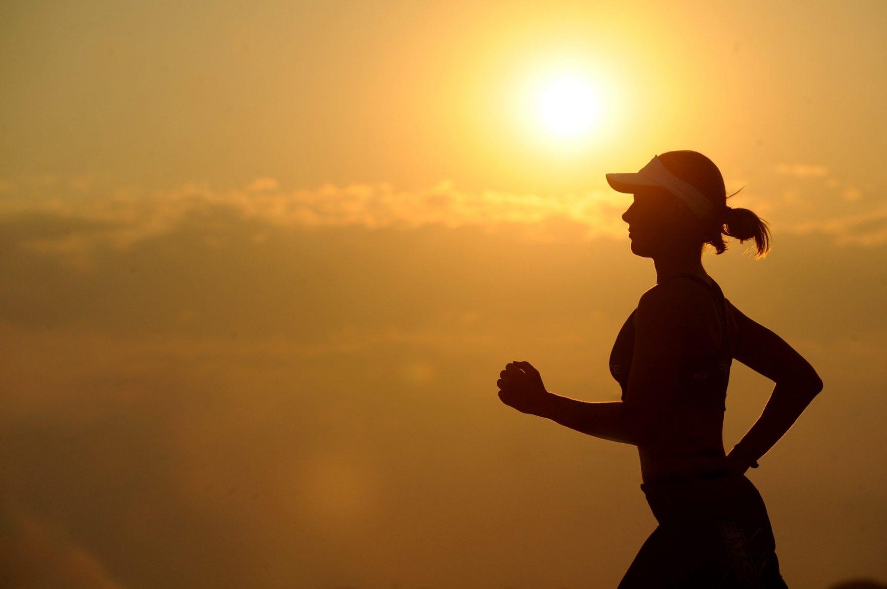 Frau joggt mit dem Sonnenuntergang im Hintergrund.