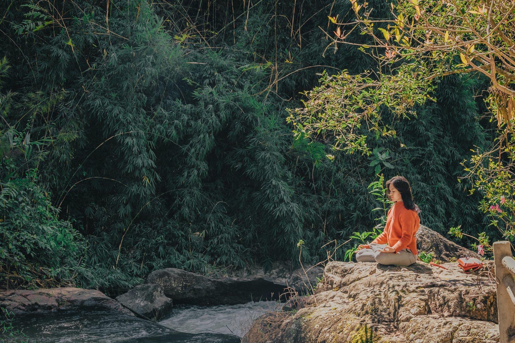 Frau sitzt auf Felsen vor einem See.