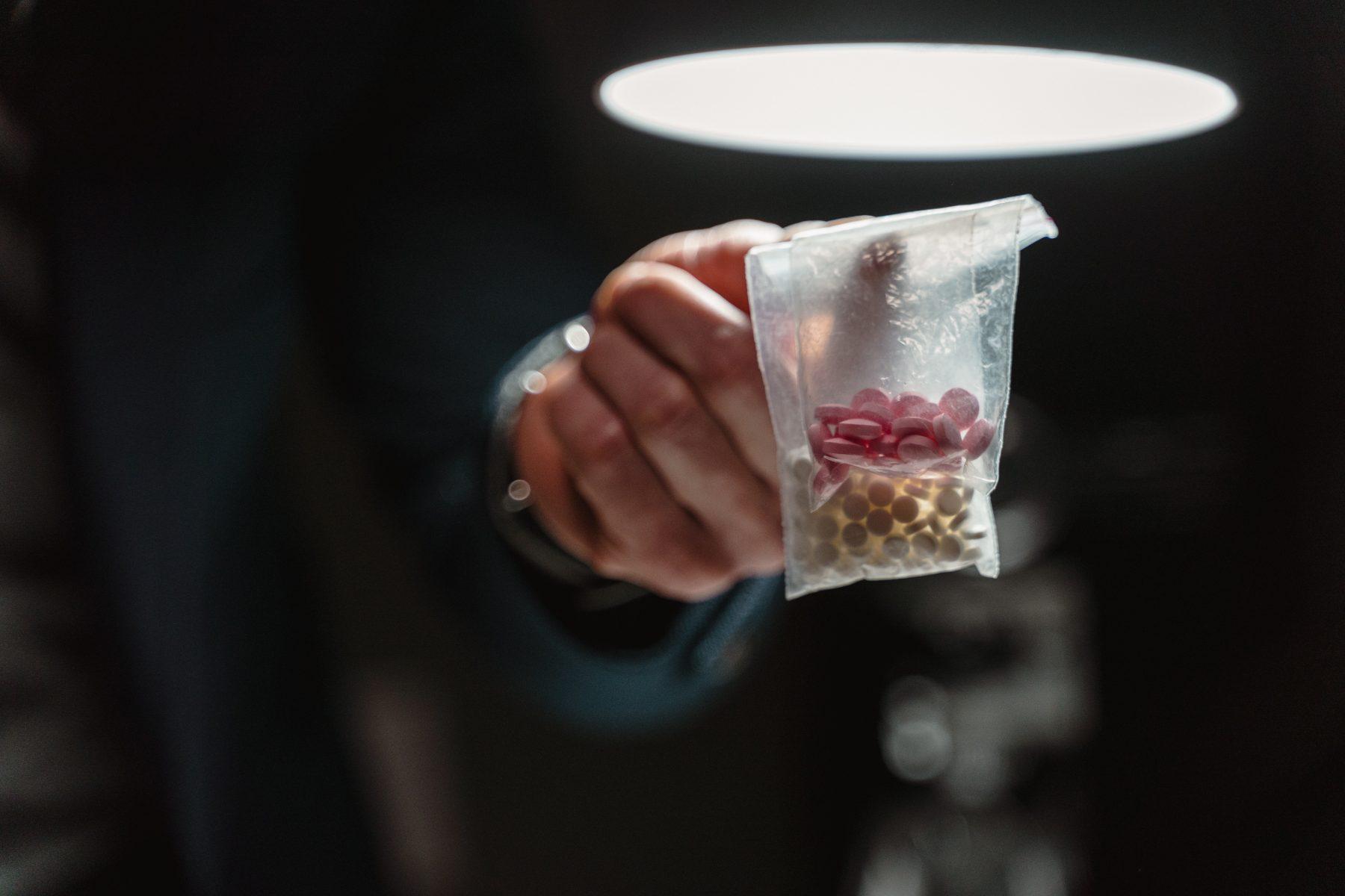 Hand, die eine Tüte Pillen hält.