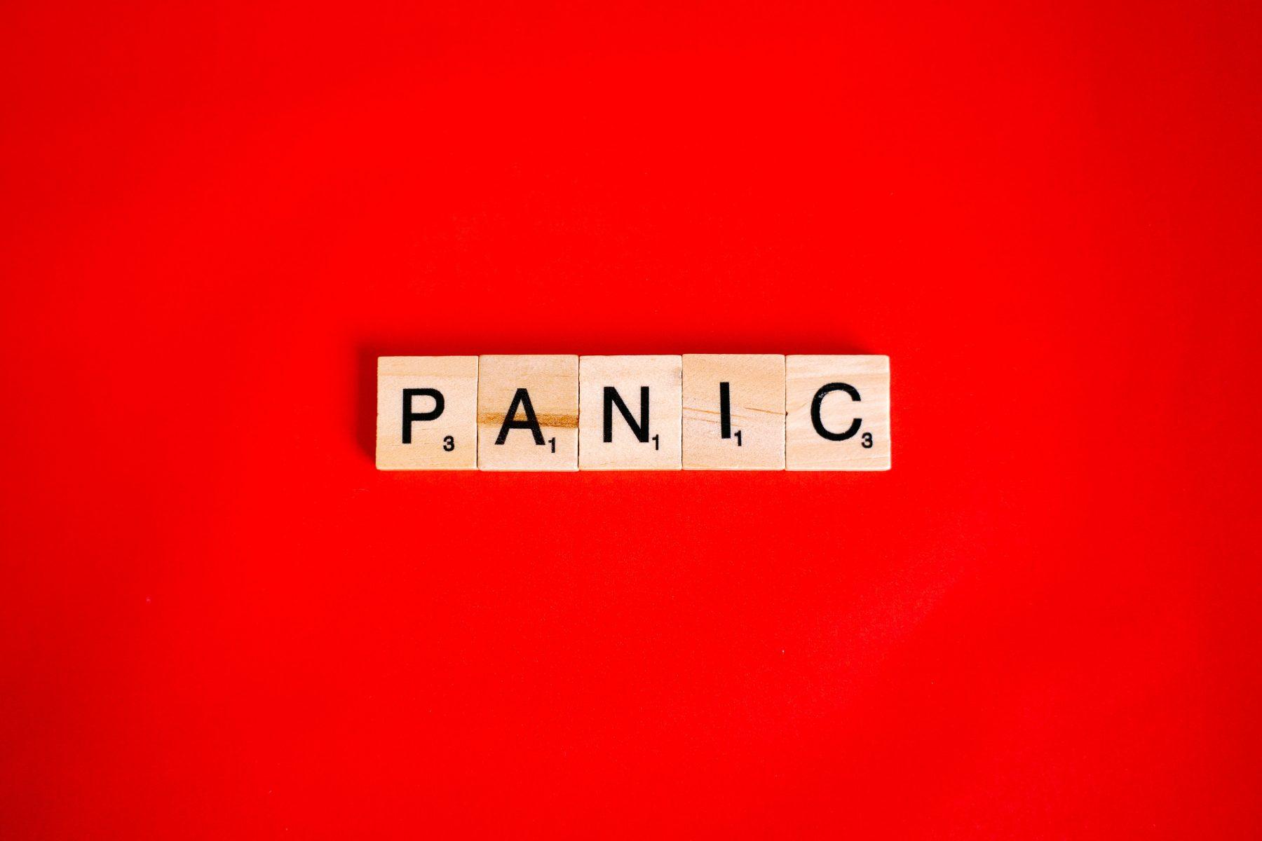 """Das Wort """"Panik"""" buchstabiert mit Scrabble-Buchstaben mit rotem Hintergrund."""