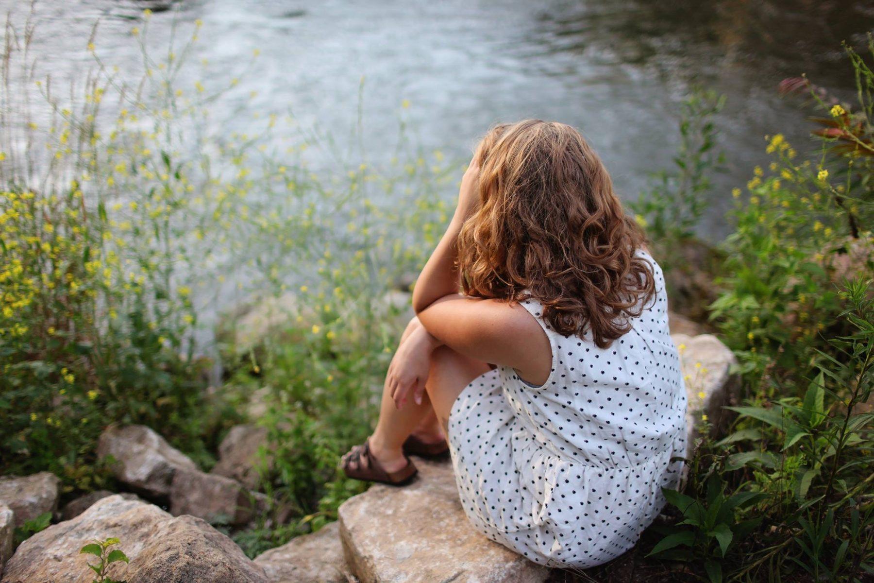 Ein Mädchen sitzt mit der Hand auf dem Kopf vor einem See.