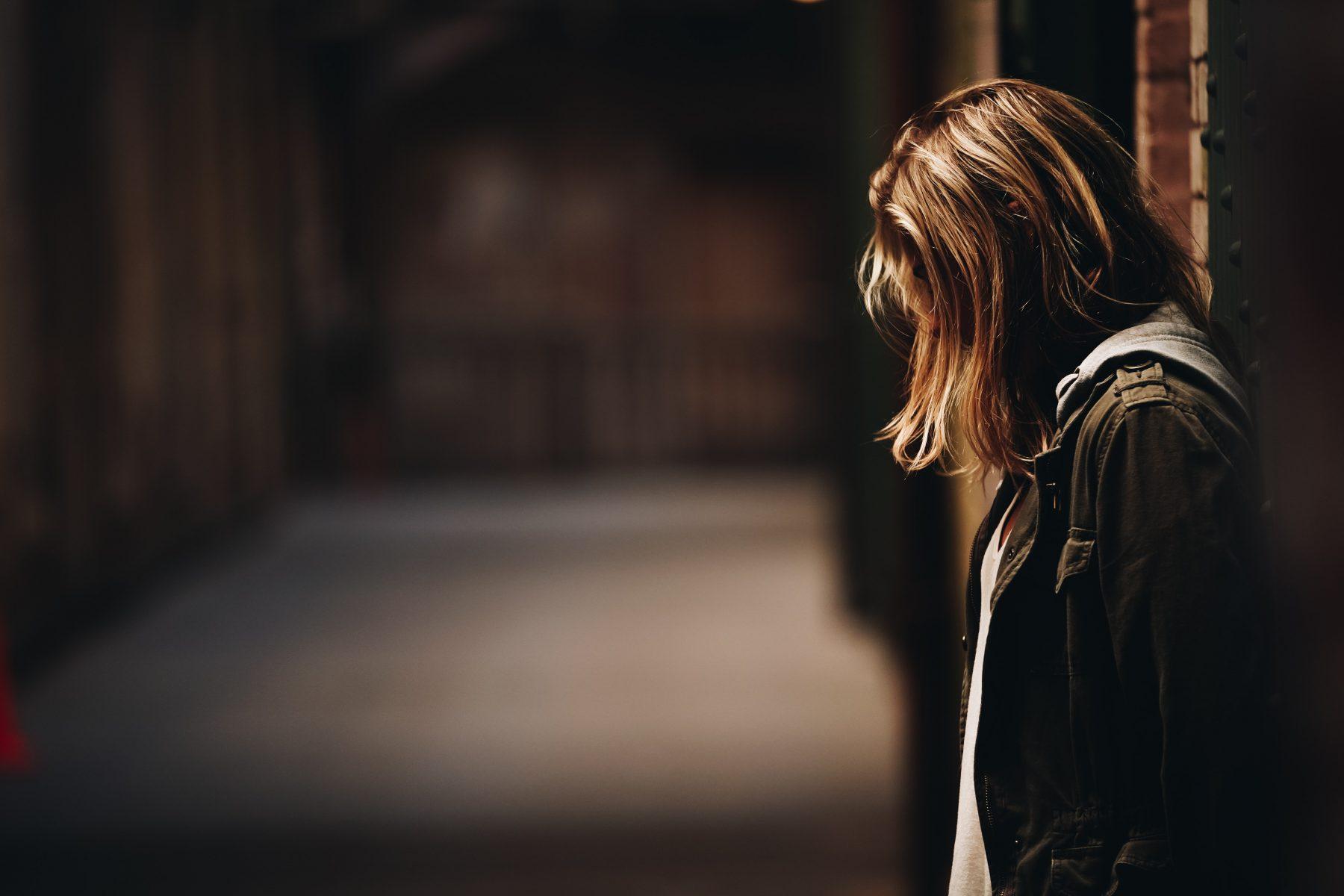 Person, die allein in einer dunklen Gasse steht.