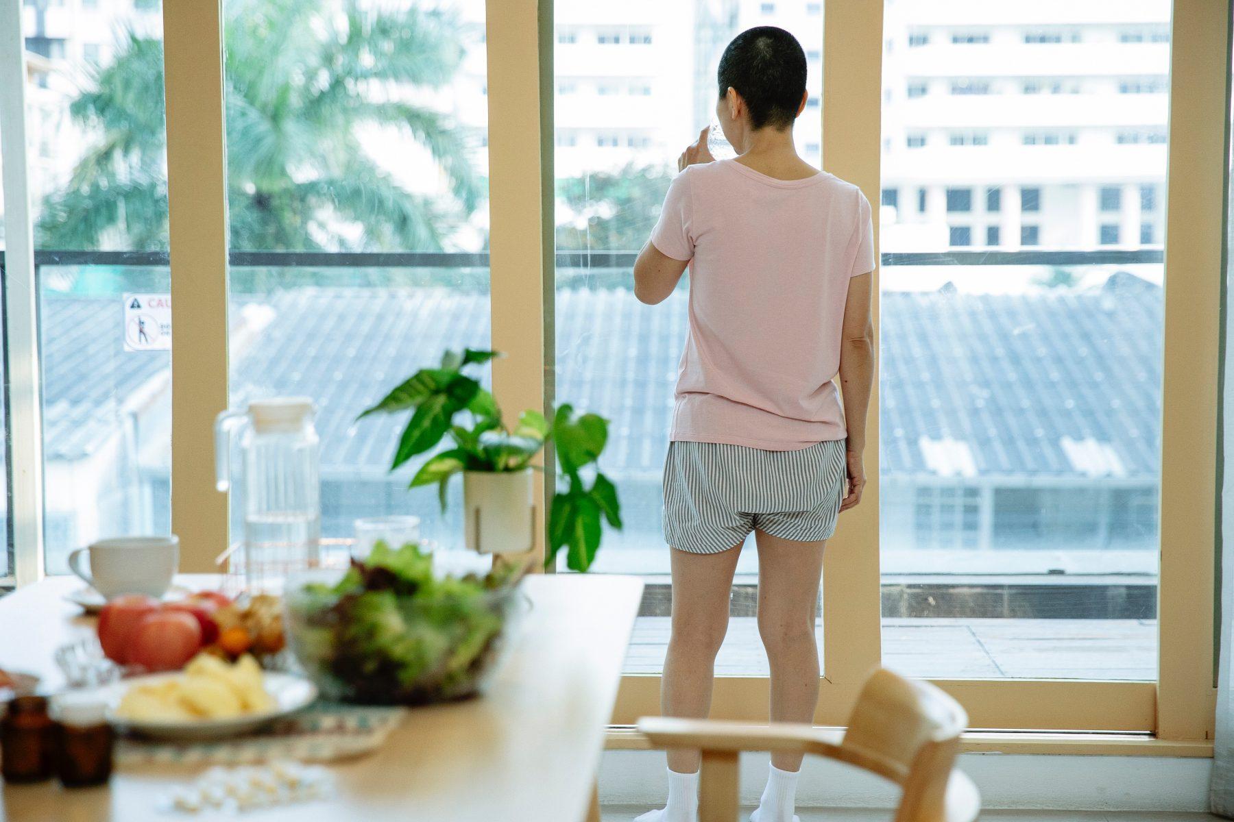 Patient schaut aus dem Fenster mit einem Tisch mit Essen im Vordergrund.