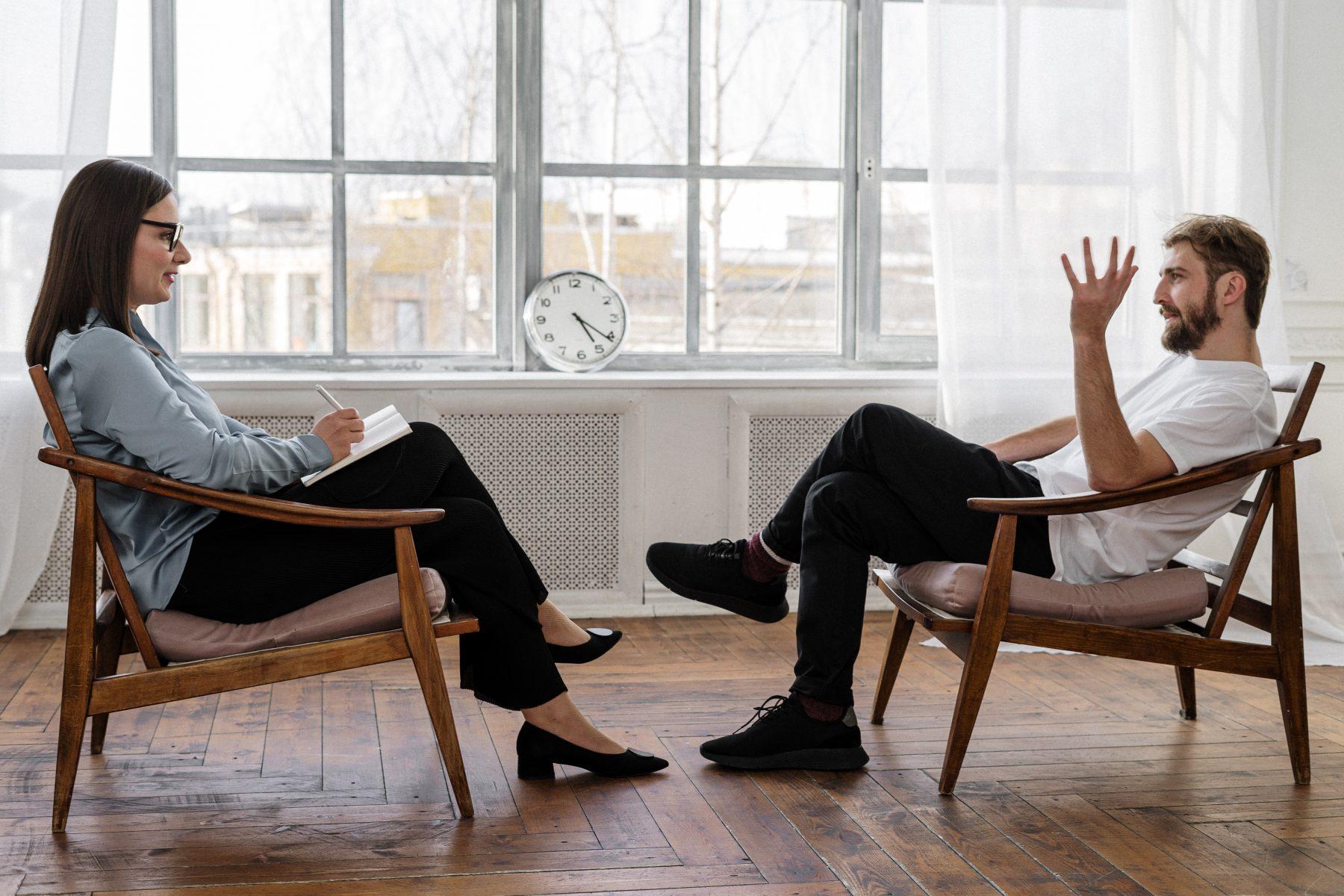 Zwei Personen sitzen sich auf einem Stuhl gegenüber und unterhalten sich.