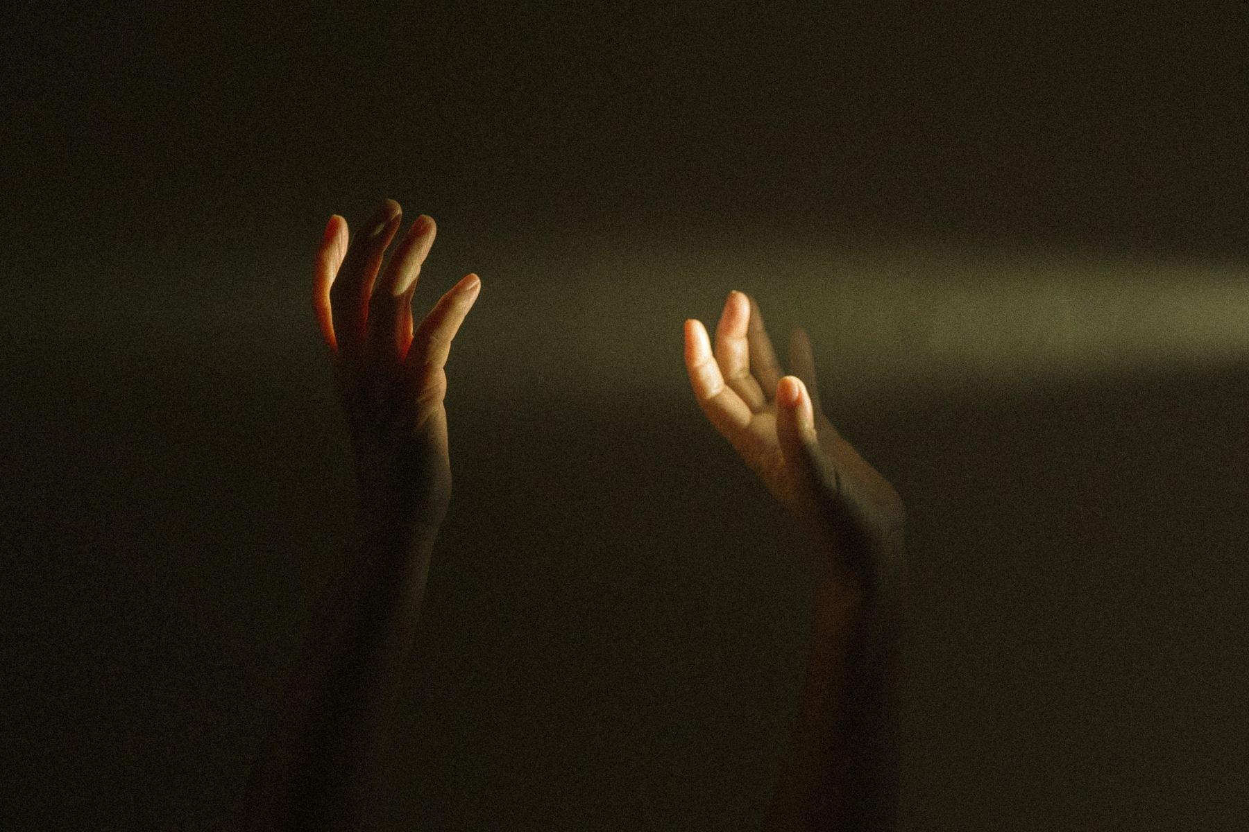 Bild von zwei erhobenen Händen im Sonnenlicht.