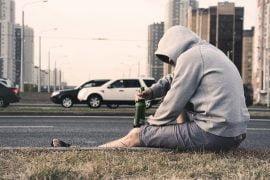 Mann sitzt auf der Seitenstraße mit einer Flasche Alkohol in der Hand.