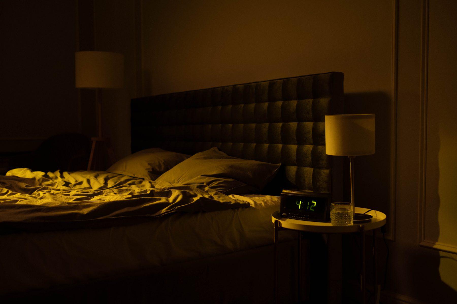 Leeres Bett und eine Uhr, die 4:12 anzeigt.