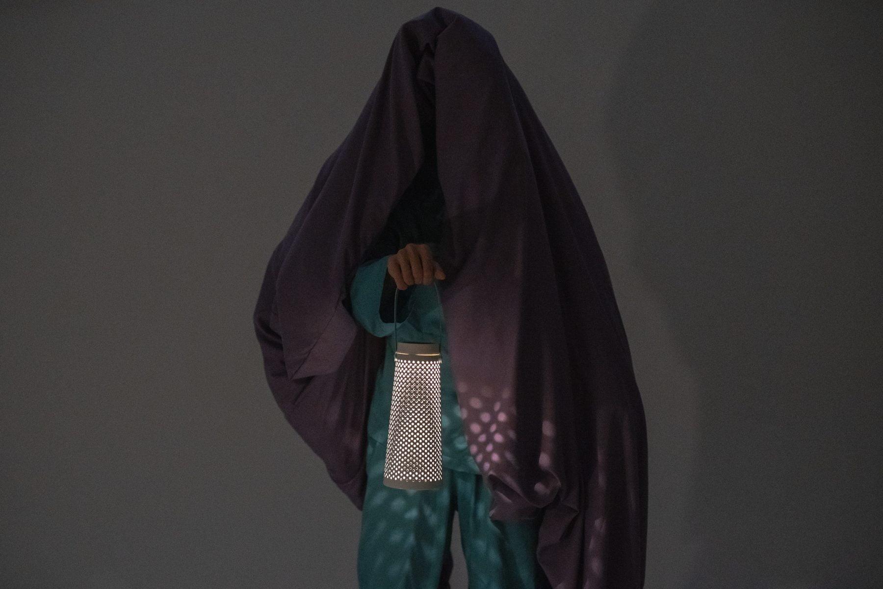 Person mit einem Laken, das den Kopf bedeckt und eine Laterne hält.
