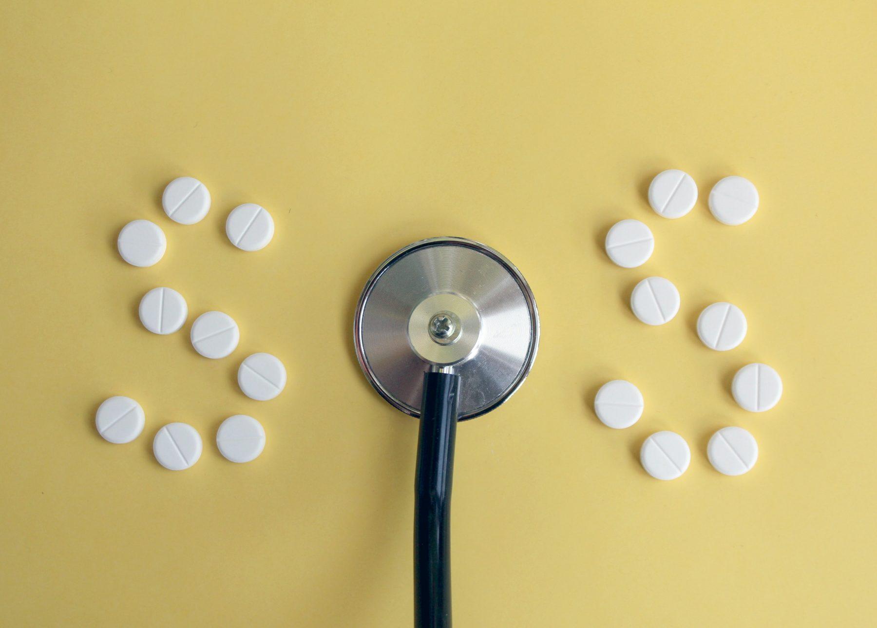 Weiße Pillen, die in einer 'S'-Form mit einem Stethoskop in der Mitte angeordnet sind, um SOS zu buchstabieren.
