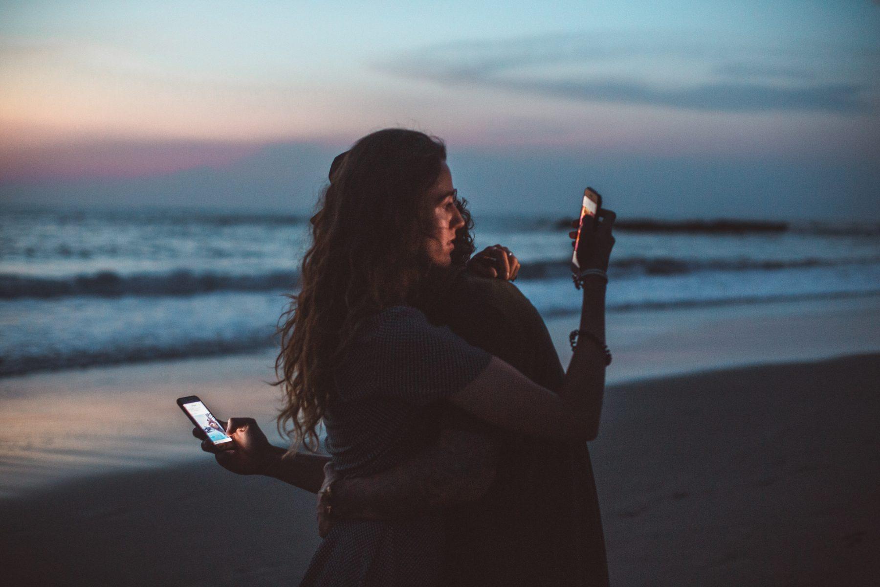 Zwei Menschen umarmen sich und halten ihre Handys in den Händen.