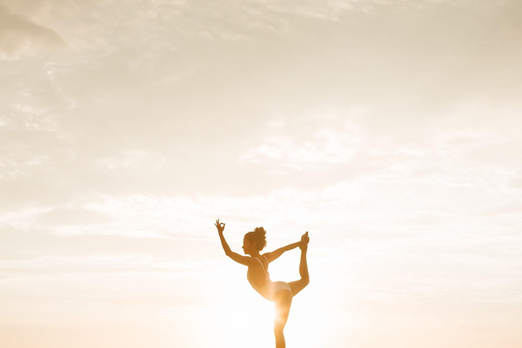 Frau macht Yoga vor dem Sonnenuntergang.