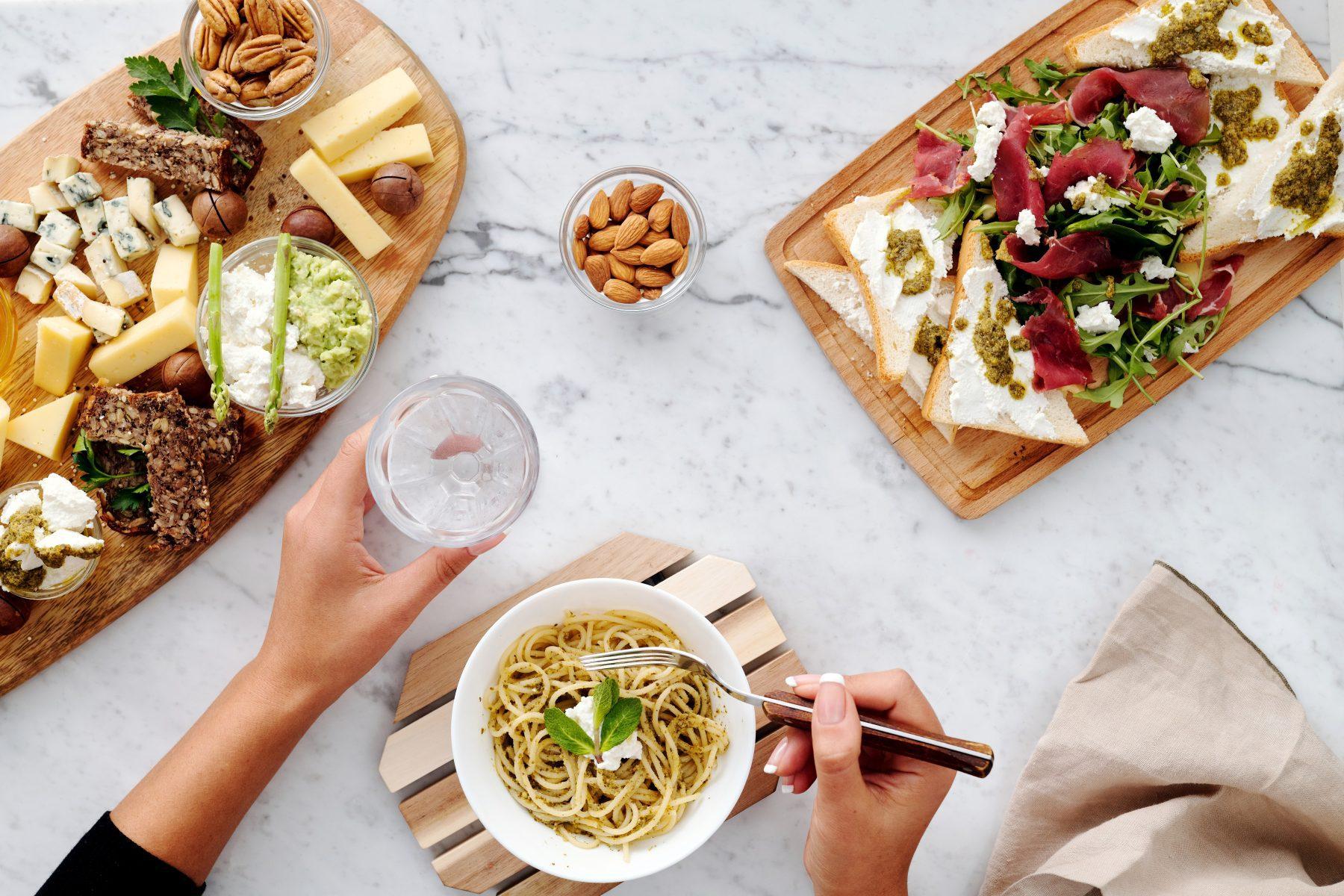 Drei Teller Essen mit einer Person beim Essen.