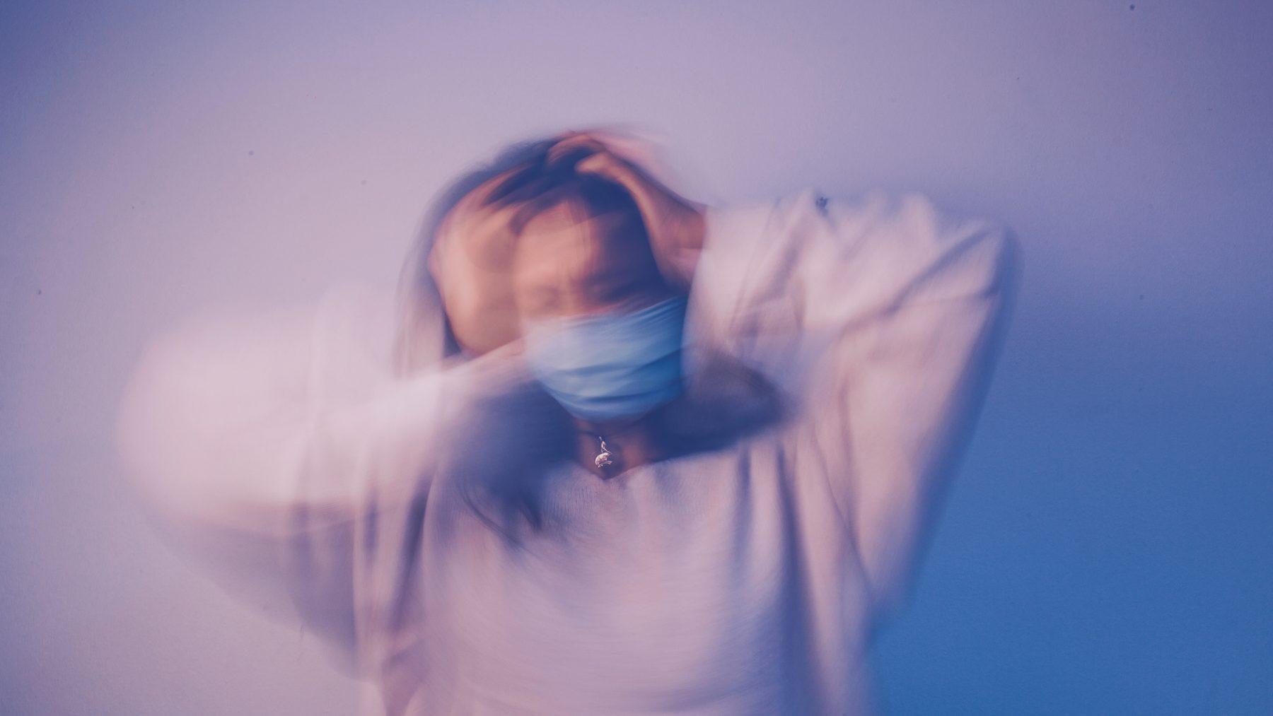 Verschwommenes Bild einer Frau mit den Händen auf dem Kopf.
